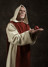 Official portrait of monk holding apple. Studio shot against dark wall.